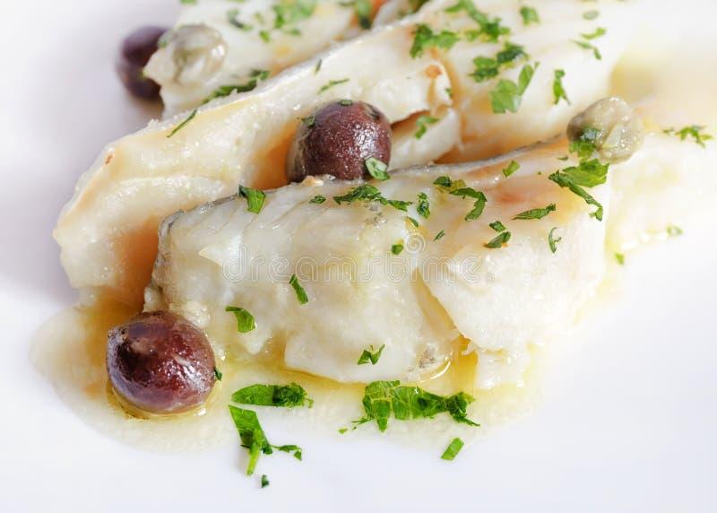 Bacalhau cozinhado no branco com adição de azeitonas e de alcaparras fotos de stock