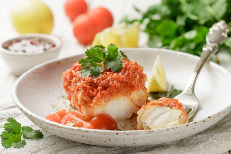Bacalhau dos peixes brancos, Pollock, nototenia, pescada, assada com cebolas, cenouras e tomates foto de stock royalty free