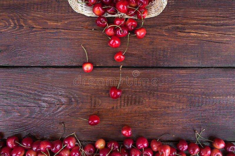 Bacca della ciliegia in un grande mucchio delle bacche con un canestro di vimini della paglia immagine stock libera da diritti