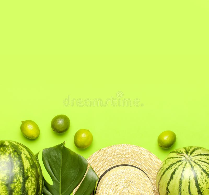 Bacca matura dell'anguria, cappello di paglia di estate, intere calce, monstera tropicale della foglia sulla disposizione piana v immagini stock