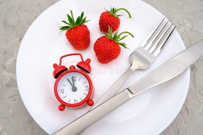 Bacca matura rossa delle fragole sul piatto bianco, sulla coltelleria e sulla sveglia rossa sulla tavola di pietra grigia del fon fotografia stock