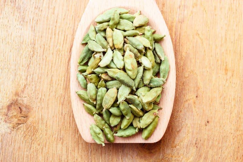 Baccelli verdi del cardamomo sul cucchiaio di legno fotografia stock