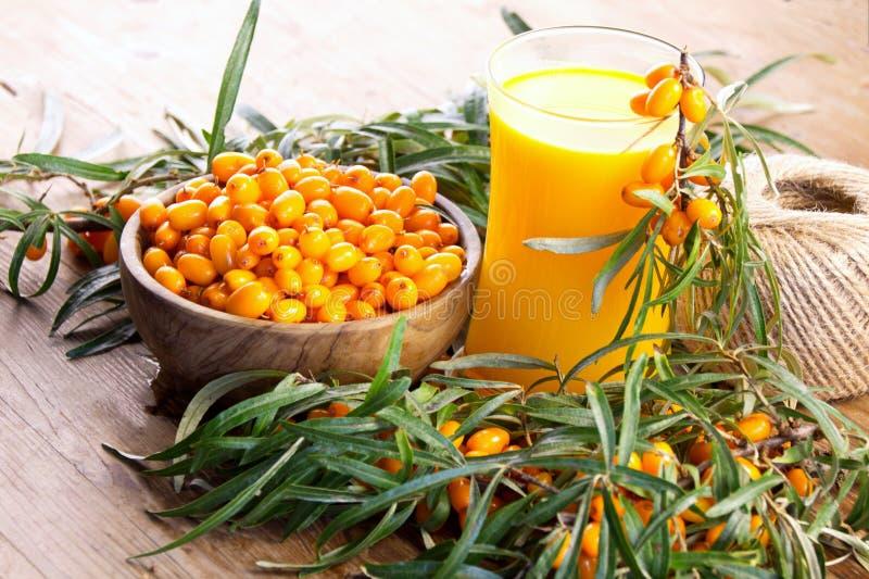 Bacche arancio fresche dell'olivello spinoso nella ciotola e sul ramo fotografia stock