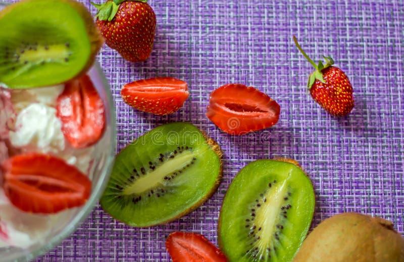 Bacche del kiwi e della fragola su un tovagliolo porpora con il dessert immagine stock libera da diritti
