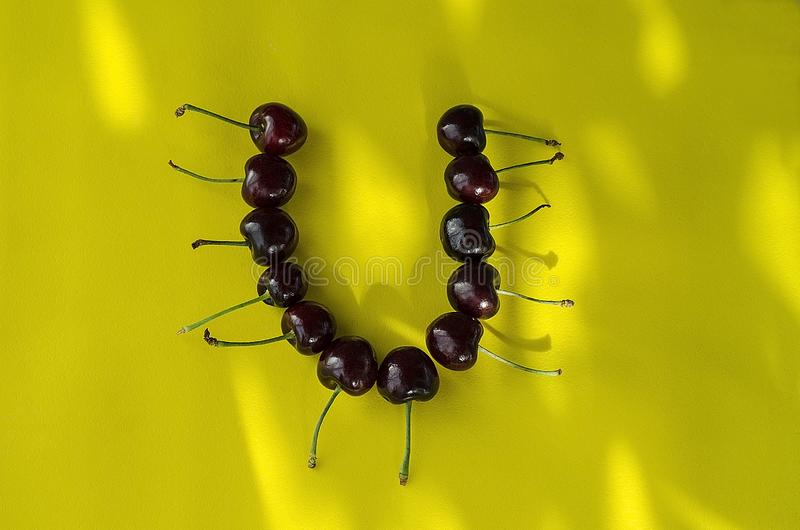 Bacche della ciliegia su un fondo giallo luminoso sotto forma di lettera U con i punti culminanti del sole immagine stock