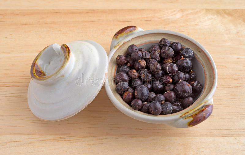 Bacche di ginepro in un piccolo piatto immagini stock