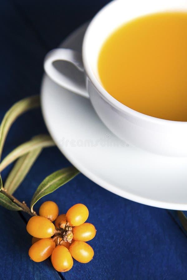 bacche mature dell'olivello spinoso accanto ad una tazza ceramica bianca con tè dalle bacche sulla tavola fotografia stock