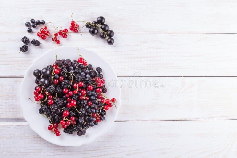Bacche, more ed uva passa del gelso su un piatto bianco sulla tavola di legno del fondo La composizione piana immagine stock