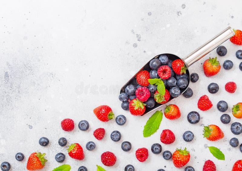 Bacche organiche crude fresche in cucchiaio d'acciaio del mestolo sul fondo del tavolo da cucina Vista superiore Prateria della f fotografie stock