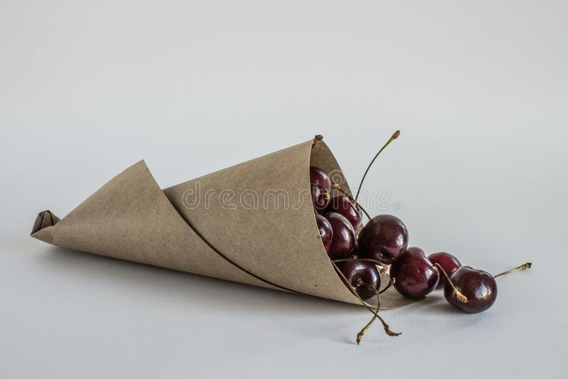 Bacche sbriciolate delle ciliege mature in un primo piano di carta della borsa rotolata fotografia stock libera da diritti