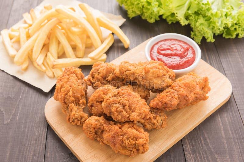 Bacchetta di pollo fritto e patate fritte sulla tavola di legno immagini stock libere da diritti