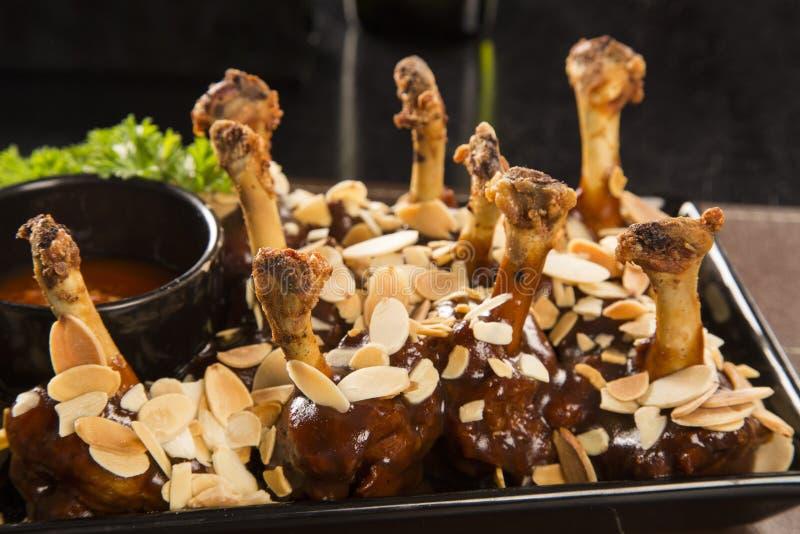 Bacchette di pollo arrostite con salsa barbecue e le mandorle fotografie stock