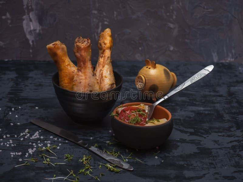 Bacchette di pollo cotte, insalata dell'uovo e della verdura, terrecotte nere e coltelleria fotografia stock