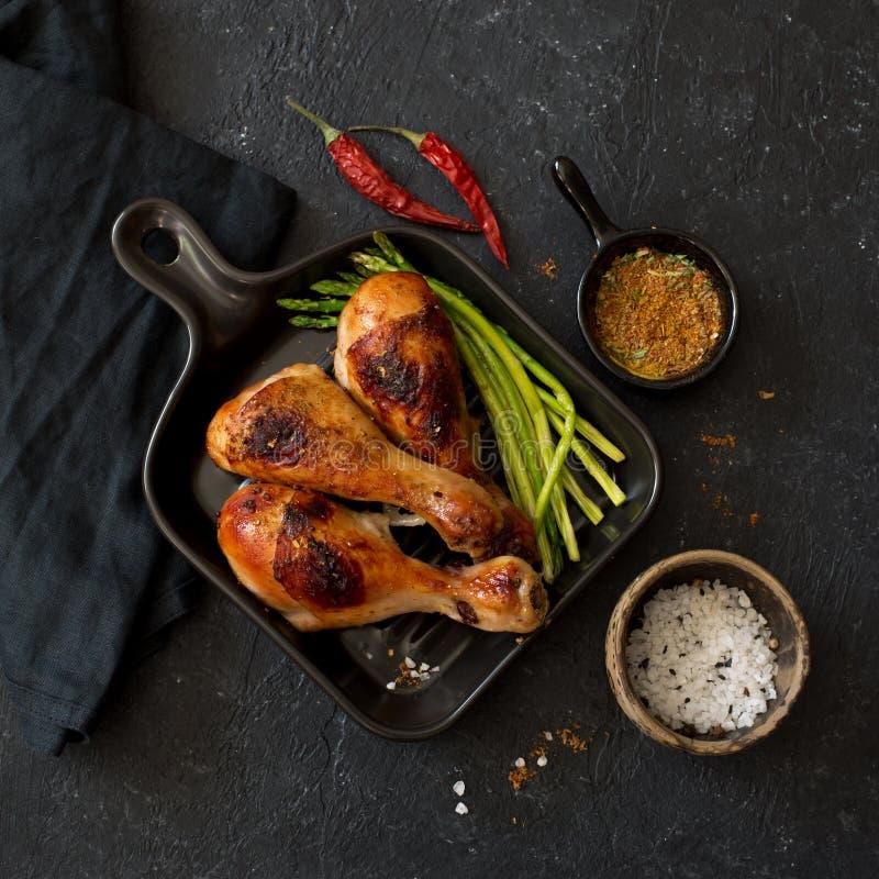Bacchette ed asparago di pollo arrostite sulla pentola ceramica fotografie stock libere da diritti