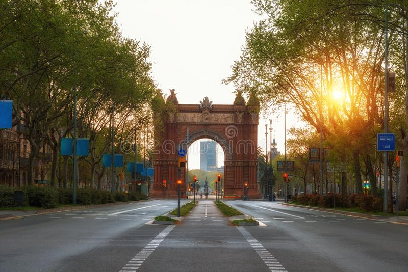 Bacelona Arc de Triomf during sunrise in the city of Barcelona in Catalonia, Spain. The arch is built in reddish brickwork in the stock photo
