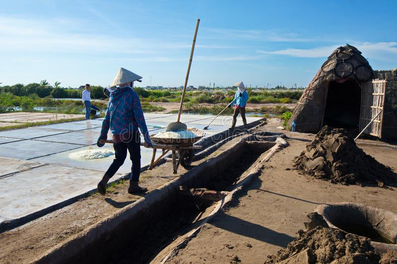 Salt workers working on salt fields. This location used to be the largest salt production site in Northern Vietnam but now almost stock images