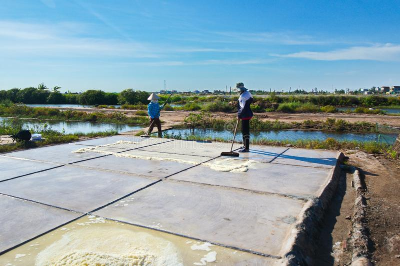 Salt workers working on salt fields. This location used to be the largest salt production site in Northern Vietnam but now almost stock image