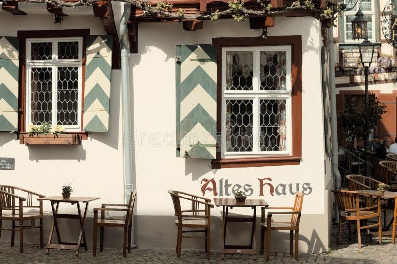 Bacharach, Германия: Половинный timbered дом с таблицами и стульями в саде стоковое фото