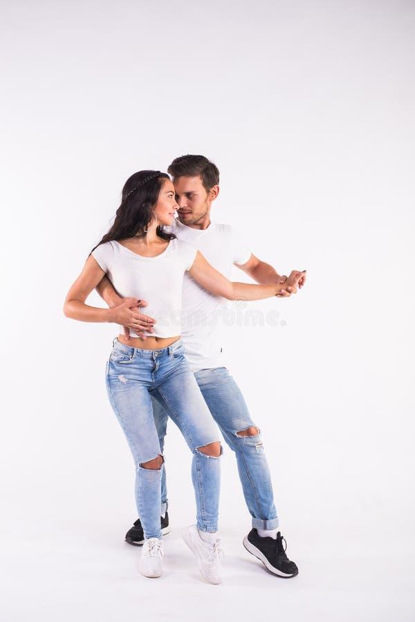 Bachata latino social de la danza del baile joven de los pares, merengue, salsa Actitud de la elegancia dos en el fondo blanco fotografía de archivo