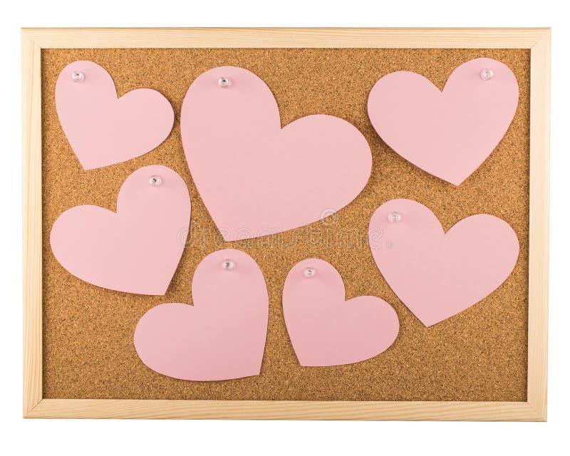 Bacheca del sughero con le note appiccicose in forma di cuore immagine stock libera da diritti
