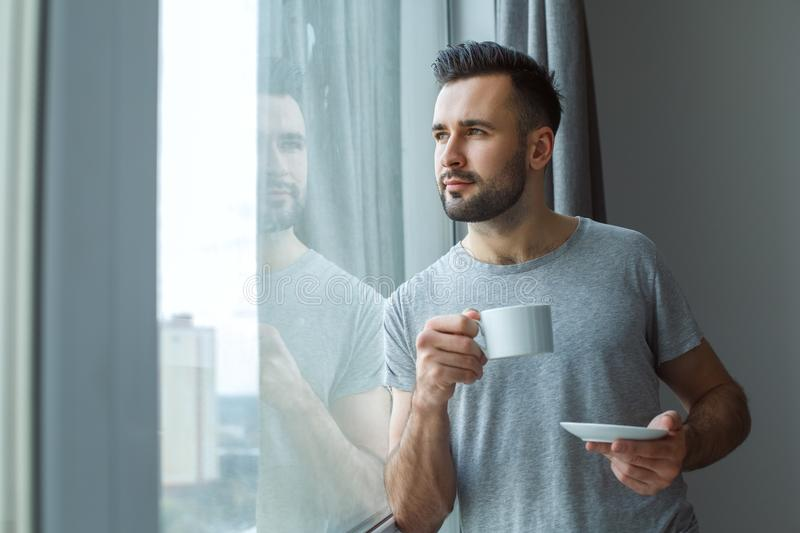 Bachelor man daily routine standing near the window single lifestyle concept drinking coffee thinking. Bachelor middle-aged man daily routine standing near the stock photos