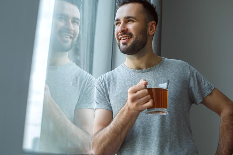 Bachelor man daily routine standing near the window single lifestyle concept drinking tea dreaming royalty free stock image