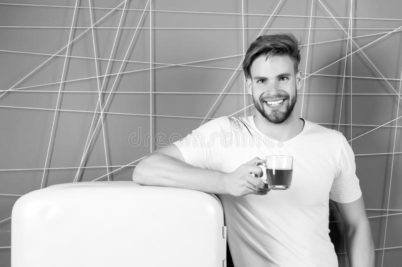 Bachelor smile with morning drink at refrigerator. Bachelor hold cup of tea or coffee at retro fridge on pink background royalty free stock images