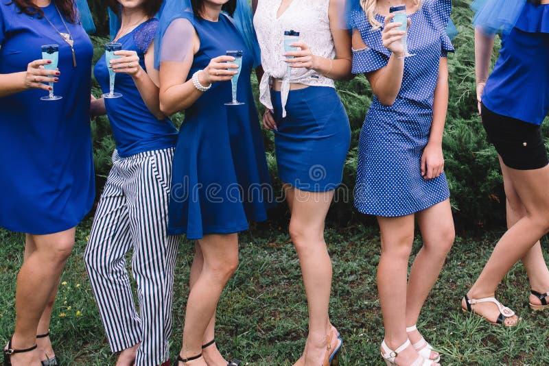 Bachelorette党,蓝色礼服的女孩有杯的香槟获得乐趣 免版税库存照片