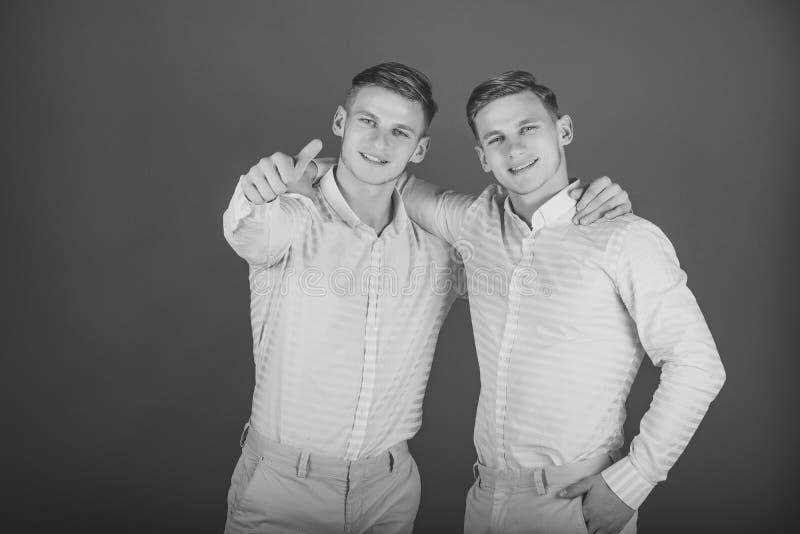 bachelors Due fratelli che sorridono e che indicano dito fotografia stock