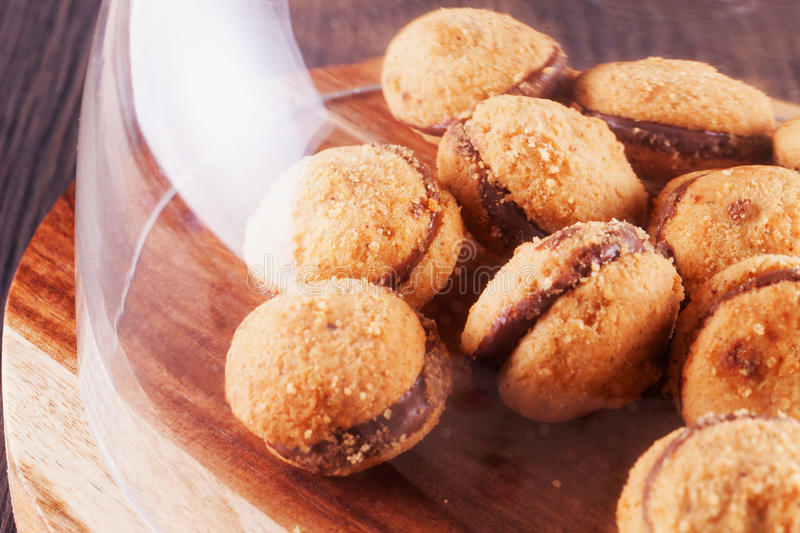 Baci di dama. Biscuits under glass jar bell, horizontal image royalty free stock photography