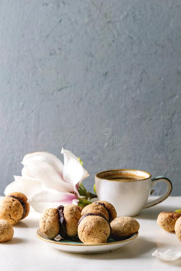 Baci di dama hazelnut biscuits. Baci di dama homemade italian hazelnut biscuits cookies with chocolate cream served in ceramic plate with cup of espresso coffee royalty free stock images