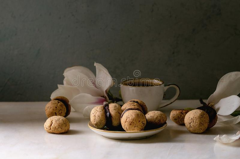 Baci di dama hazelnut biscuits. Baci di dama homemade italian hazelnut biscuits cookies with chocolate cream served in ceramic plate with cup of espresso coffee royalty free stock photography