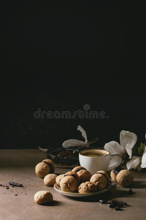 Baci di dama hazelnut biscuits. Baci di dama homemade italian hazelnut biscuits cookies with chocolate cream served in ceramic plate with cup of espresso coffee stock images
