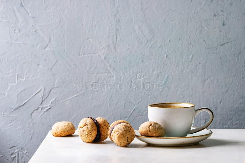 Baci di dama hazelnut biscuits. Baci di dama homemade italian hazelnut biscuits cookies with chocolate cream served in ceramic plate with cup of espresso coffee stock image