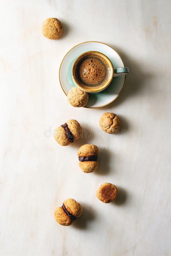 Baci di dama hazelnut biscuits. Baci di dama homemade italian hazelnut biscuits cookies with chocolate cream served in ceramic plate with cup of espresso coffee stock photos