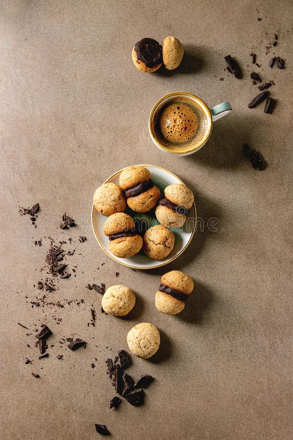Baci di dama hazelnut biscuits. Baci di dama homemade italian hazelnut biscuits cookies with chocolate cream served in ceramic plate with cup of espresso coffee royalty free stock photo