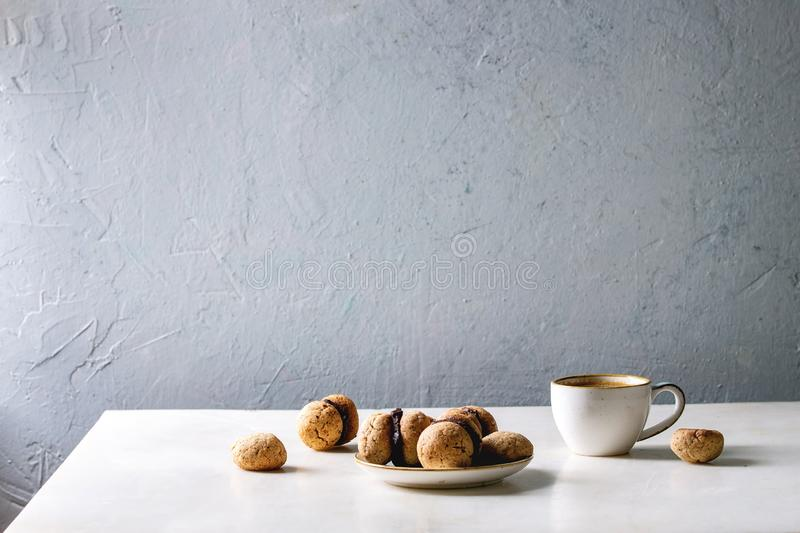 Baci di dama hazelnut biscuits. Baci di dama homemade italian hazelnut biscuits cookies with chocolate cream served in ceramic plate with cup of espresso coffee stock photography