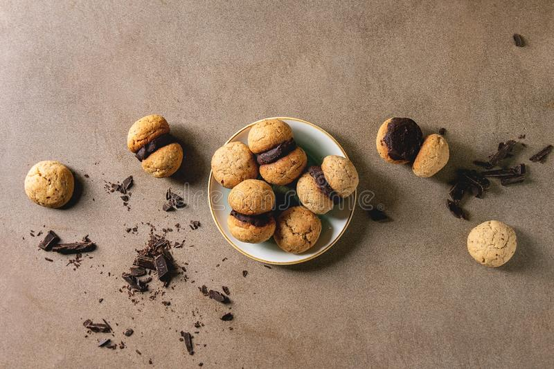 Baci di dama hazelnut biscuits. Baci di dama homemade italian hazelnut biscuits cookies with chocolate cream served in ceramic plate over brown texture royalty free stock photography