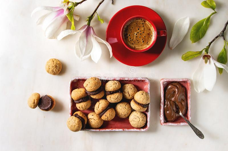 Baci di dama hazelnut biscuits. Baci di dama homemade italian hazelnut biscuits cookies with chocolate cream served in ceramic plate with red cup of espresso royalty free stock photos
