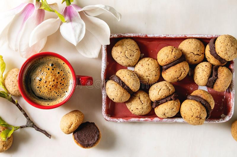 Baci di dama hazelnut biscuits. Baci di dama homemade italian hazelnut biscuits cookies with chocolate cream served in ceramic plate with red cup of espresso stock image