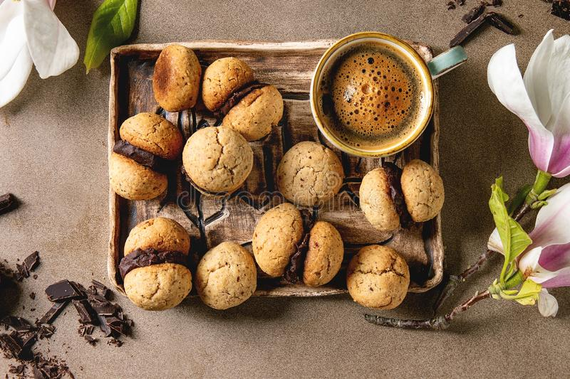 Baci di dama hazelnut biscuits. Baci di dama homemade italian hazelnut biscuits cookies with chocolate cream served in ceramic tray with cup of espresso coffee stock photos