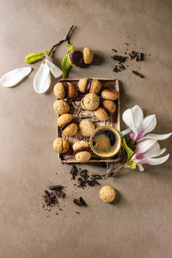 Baci di dama hazelnut biscuits. Baci di dama homemade italian hazelnut biscuits cookies with chocolate cream served in ceramic tray with cup of espresso coffee royalty free stock photography