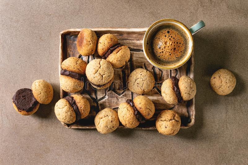 Baci di dama hazelnut biscuits. Baci di dama homemade italian hazelnut biscuits cookies with chocolate cream served in ceramic tray with cup of espresso coffee stock photography