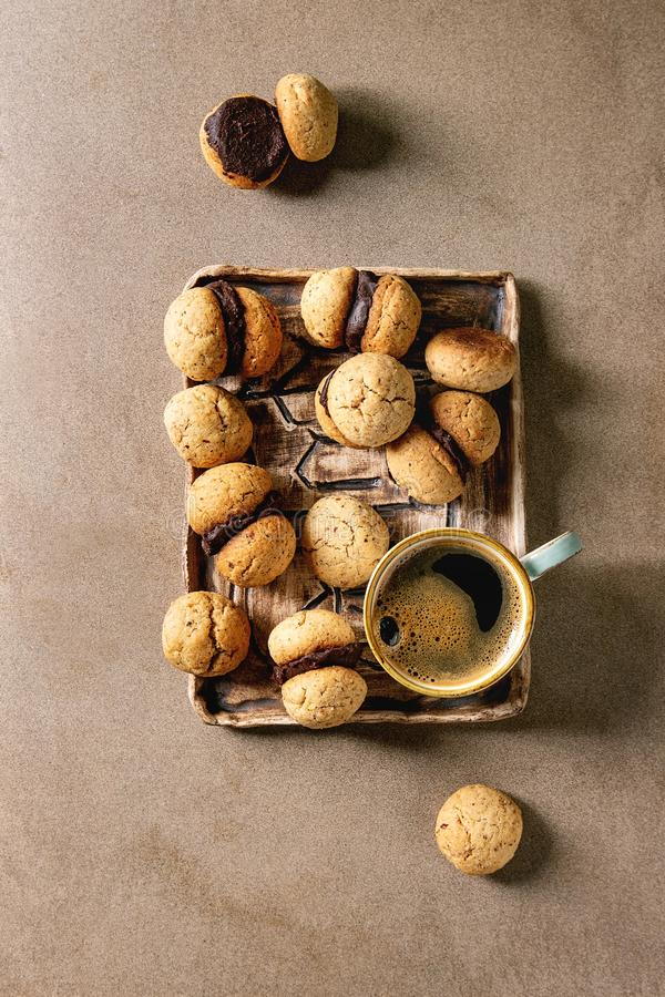 Baci di dama hazelnut biscuits. Baci di dama homemade italian hazelnut biscuits cookies with chocolate cream served in ceramic tray with cup of espresso coffee royalty free stock photo