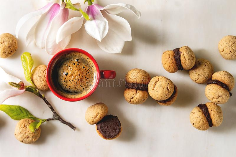Baci di dama hazelnut biscuits. Baci di dama homemade italian hazelnut biscuits cookies with chocolate cream served with red cup of espresso coffee and magnolia stock images