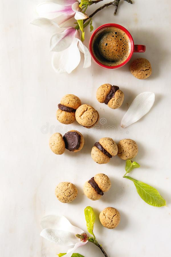 Baci di dama hazelnut biscuits. Baci di dama homemade italian hazelnut biscuits cookies with chocolate cream served with red cup of espresso coffee and magnolia royalty free stock photos