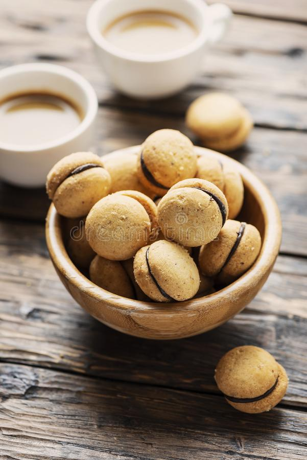 Baci di dama. Homemade italian hazelnut biscuits cookies with chocolate cream, rustic style and selective image royalty free stock photos