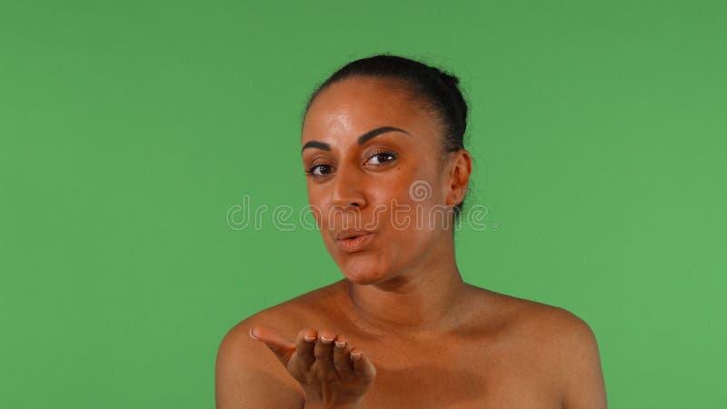 Baci di salto della donna africana splendida alla macchina fotografica immagine stock