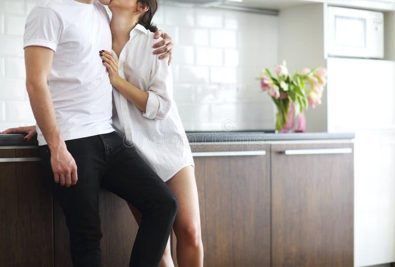 Baci ed abbracci delle coppie alla cucina di mattina fotografie stock