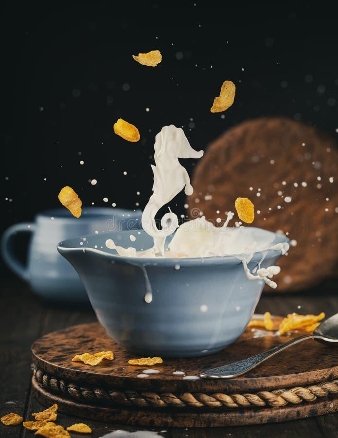 Bacia azul de flocos de milho com respingo do leite fotos de stock